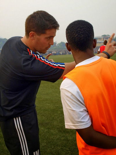 Coach McKinstry provides half time advice to Santigie Koroma (CBF) before his debut for Sierra Leone U20 [versus Guinea in 2015 CAF U-20 first round qualifying (Picture: Myrthe van Vliet)]